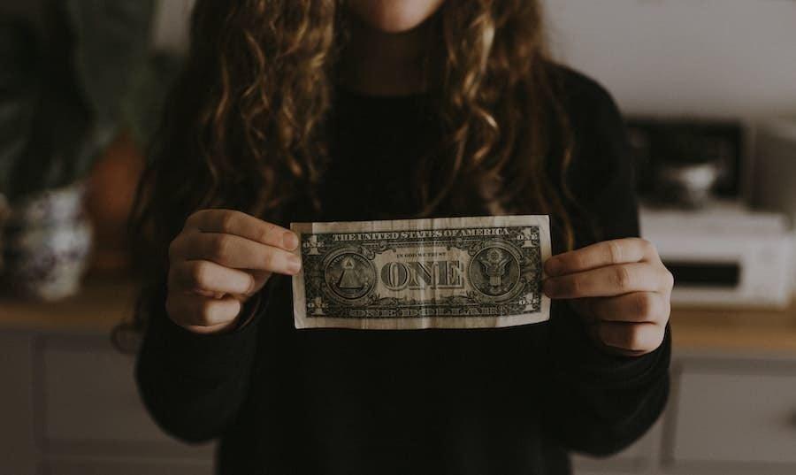 girl holding one dollar