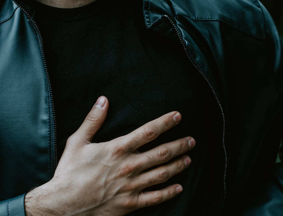 man hand on chest cause of acking heart