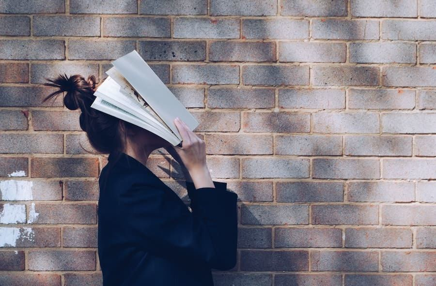 woman covers head with book